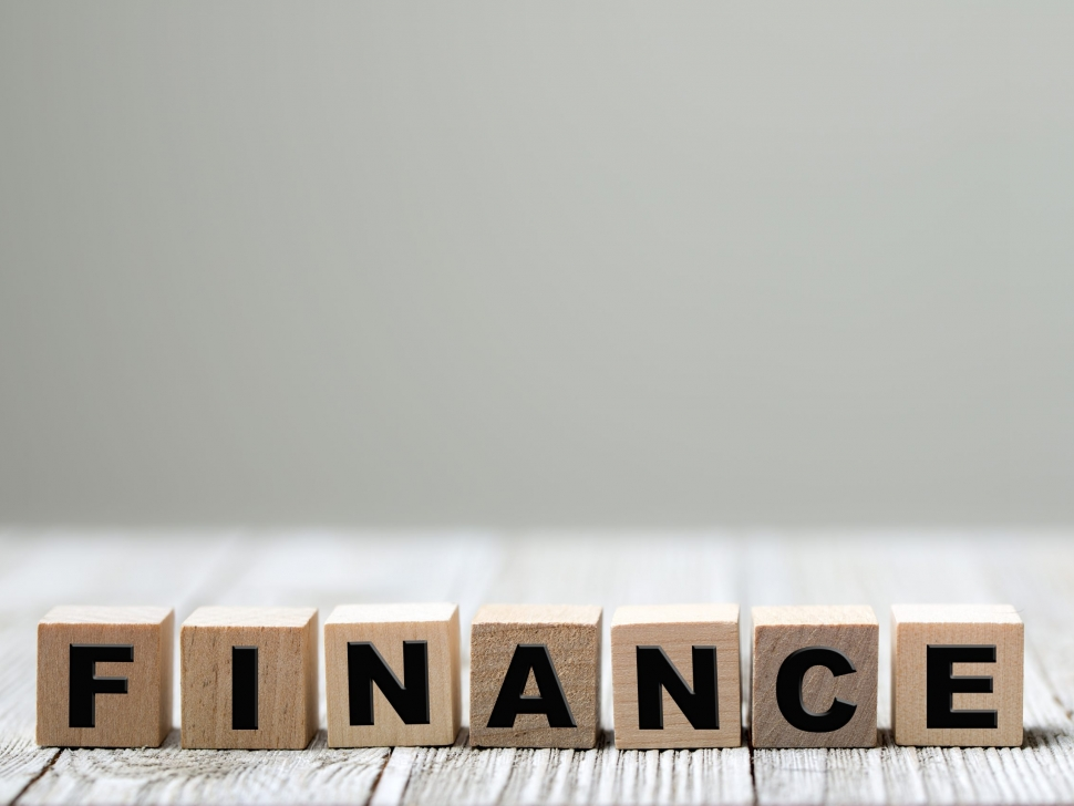Finance word on square wooden blocks on a wooden background